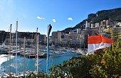 Monte Carlo, Monaco - December 22 2019: Port Hercules with Monaco flag and clear blue sky