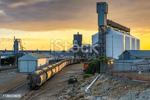 The morning sun squeezes through the cloud cover to cast soft morning light over an industrial port scene