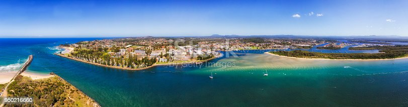 Port Macquarie regional town in NSW, Australia, on Mid North Coast at the river mouth of Hastings river in to Pacific ocean. Aerial wide panorama of town riverfront around downtown and wharf.
