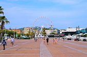 Cannes, France - July 18 2019: Old Port of Cannes promenade with Ferris wheel and people summer daytime view