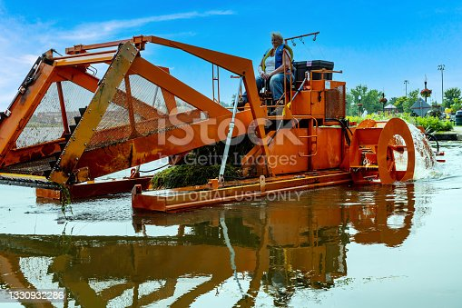 istock Port Perry Marina in summer, Weed Cutter Working on Lake Scugog Removing aquatic Weeds, Port Perry, Canada 1330932286