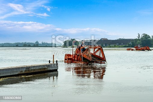 istock Port Perry Marina in summer, Weed Cutter Working on Lake Scugog Removing aquatic Weeds, Port Perry, Canada 1330932855