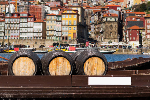 Port Wine barrels in a boat in the Douro River with the city of Porto in the background stock photo