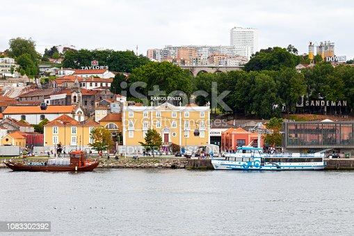 Vila Nova de Gaia, Portugal - June 03 2018: A Rabelos (boat used to transport barrels of port) next to a tourist boat moored alongside the Port wine district.