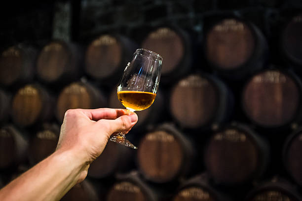 port wine with glass port wine in wine cellar, glass of alcohol in cellar, glass of wine in hand, wine degustation brandy stock pictures, royalty-free photos & images