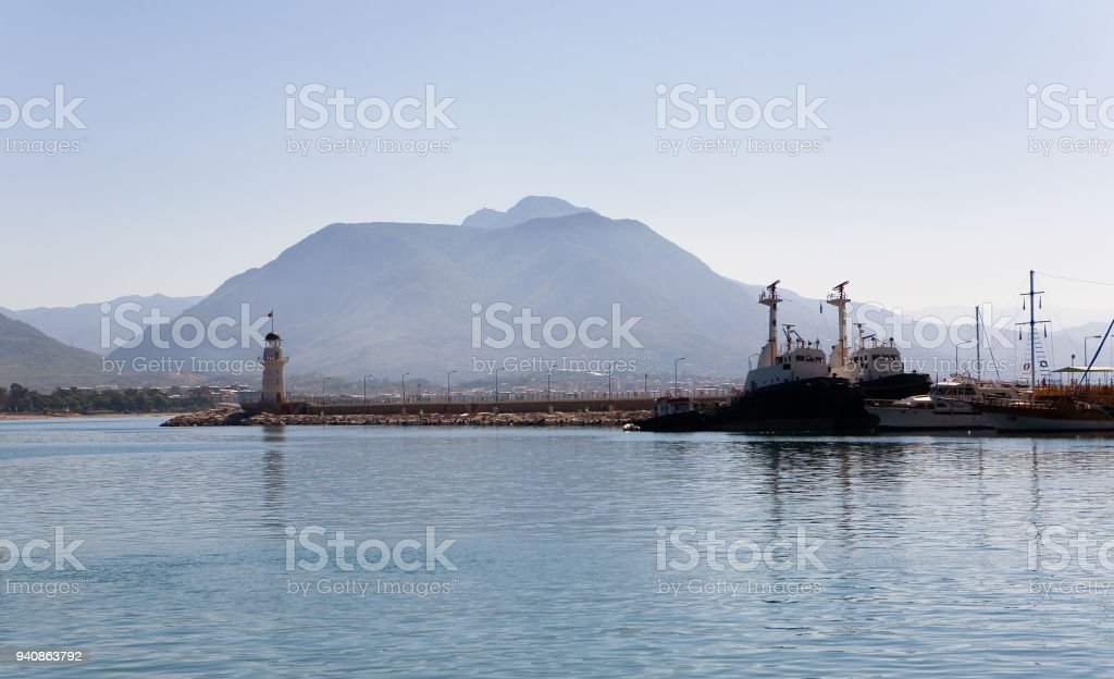 Port with a lighthouse and ships against the backdrop of the mountains. stock photo