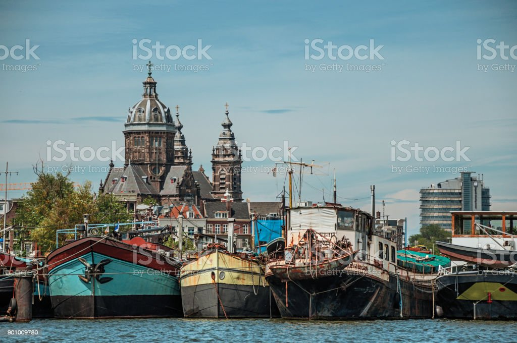 Port with rusty moored ships, church towers and building on canal under a sunny blue sky in Amsterdam. stock photo