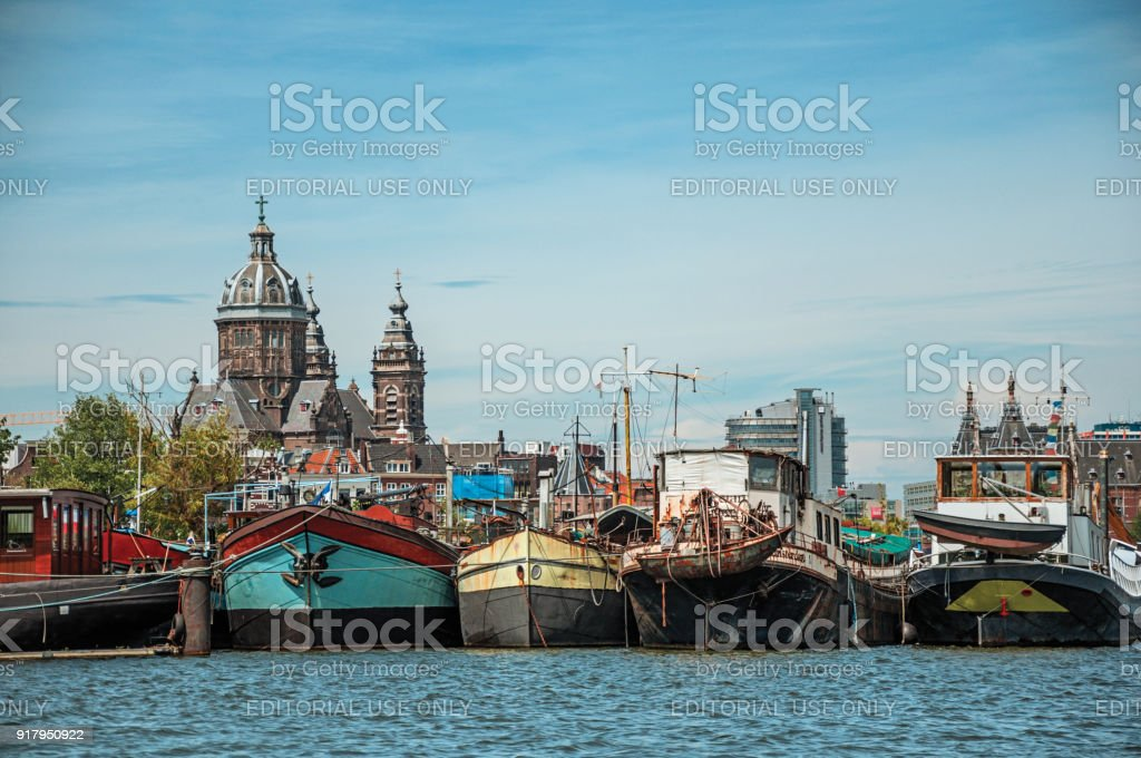 Port with rusty moored ships in a canal and sunny blue sky in Amsterdam. stock photo