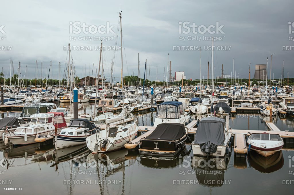 Port with several decks and moored boats in a cloudy day at Drimmelen. stock photo