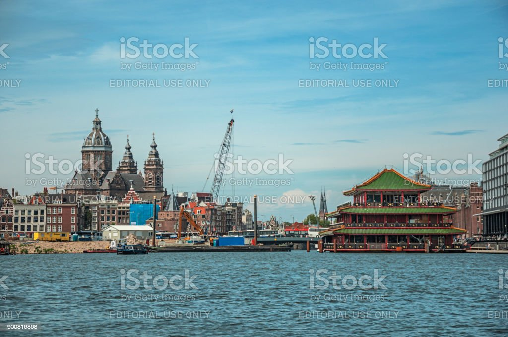 Port with ships, church towers and pagoda building in sunny day at Amsterdam. stock photo