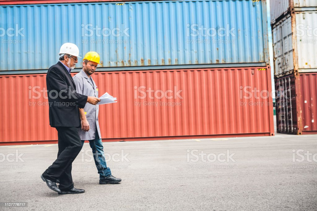 Port Workers Passing Cargo Containers stock photo