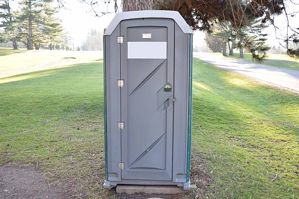 Porta Potty Green And Grey At Golf Course Under Tree Porta Potty Green And Grey At Golf Course Under Tree. portable toilet stock pictures, royalty-free photos & images