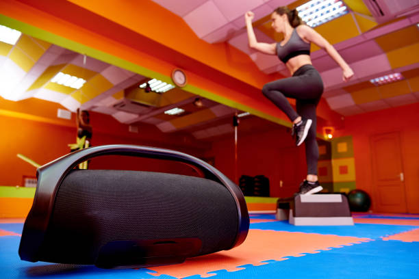 Portable acoustics in the aerobics room on the background of a blurred girl training on a step platform. stock photo