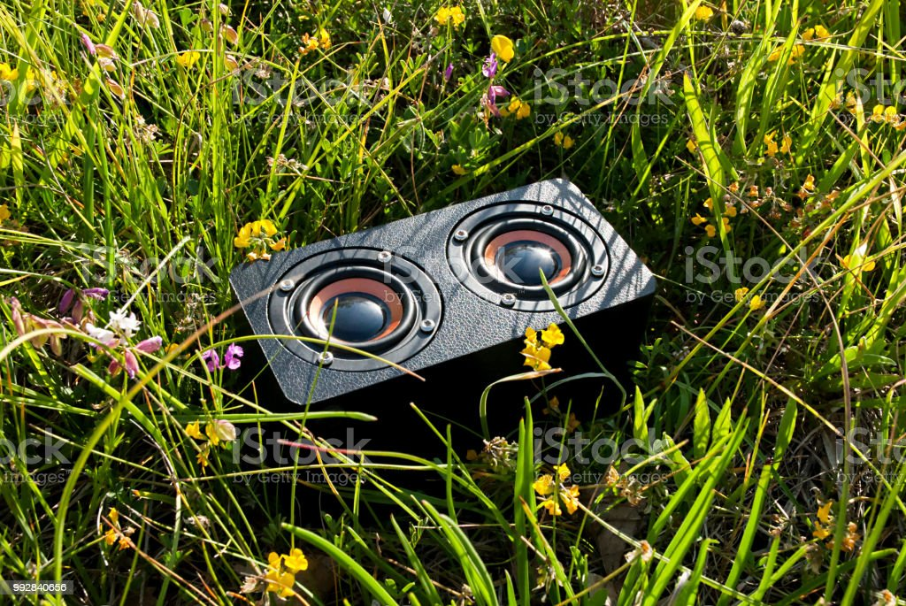 portable audio speaker in the grass stock photo
