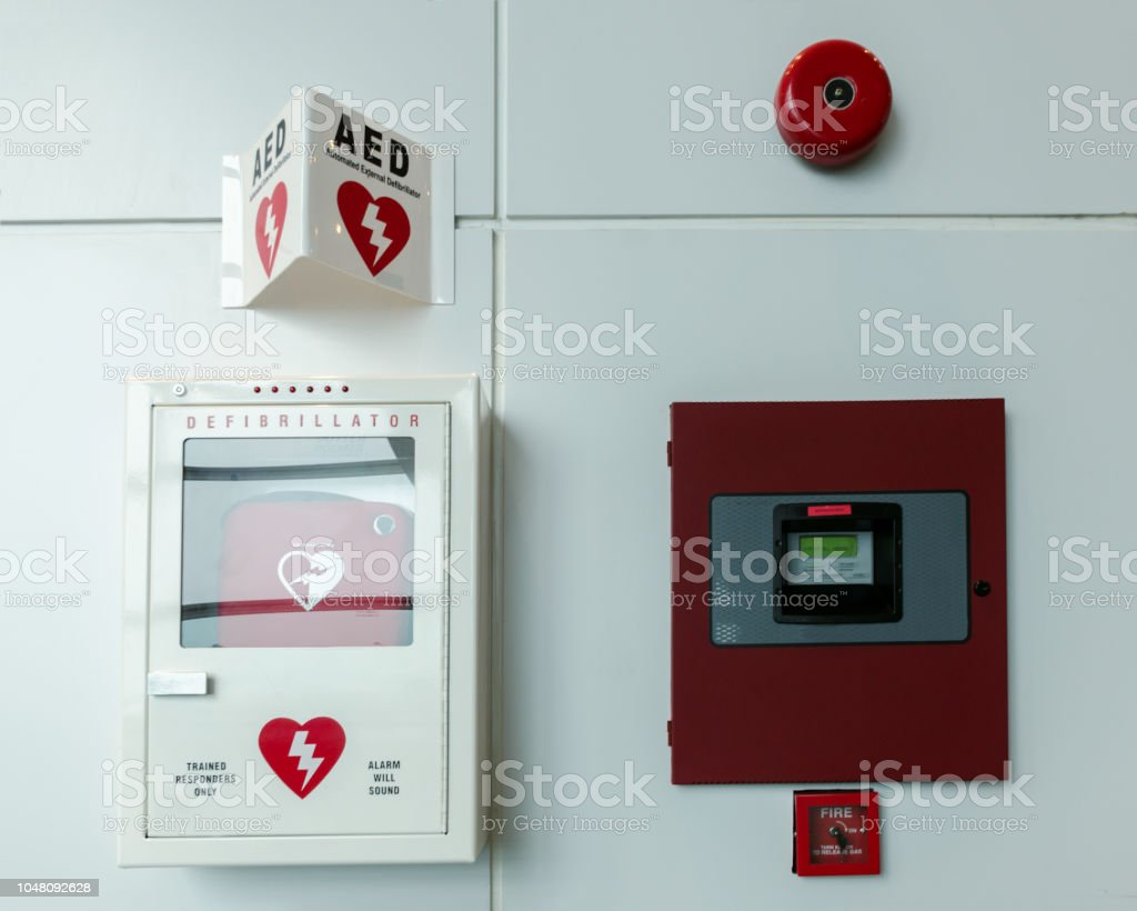 Portable automated external defibrillator (AED) and fire alarm system mounted on the wall in public restroom at airport. stock photo