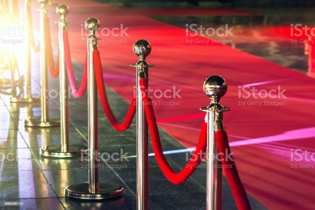 Portable Barrier for Queue Control. Red security rope by red carpet. stock photo