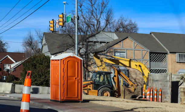 Portable bathroom at construction site at intersectio of urban roads with backhoe in background and traffic cones around Portable bathroom at construction site at intersectio of urban roads with backhoe in background and traffic cones around portable toilet stock pictures, royalty-free photos & images