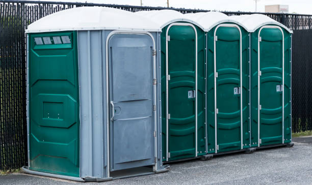Portable bathrooms in a parking lot Green and gray potties set up in a parking lot with the end one for handicapped. portable toilet stock pictures, royalty-free photos & images