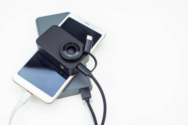 tragbare ladegeräte. smartphone mit actionkamera, die auf weißem hintergrund mit der strombank verbunden ist. - desktop hintergrund hd stock-fotos und bilder
