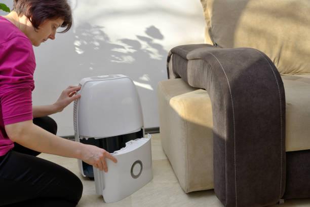Portable dehumidifier collect water from air inside of living room picture id907022088?b=1&k=6&m=907022088&s=612x612&w=0&h=utg1x3b 0bfofwjpyiogczzcmffoojpzi21sx2vgfb8=