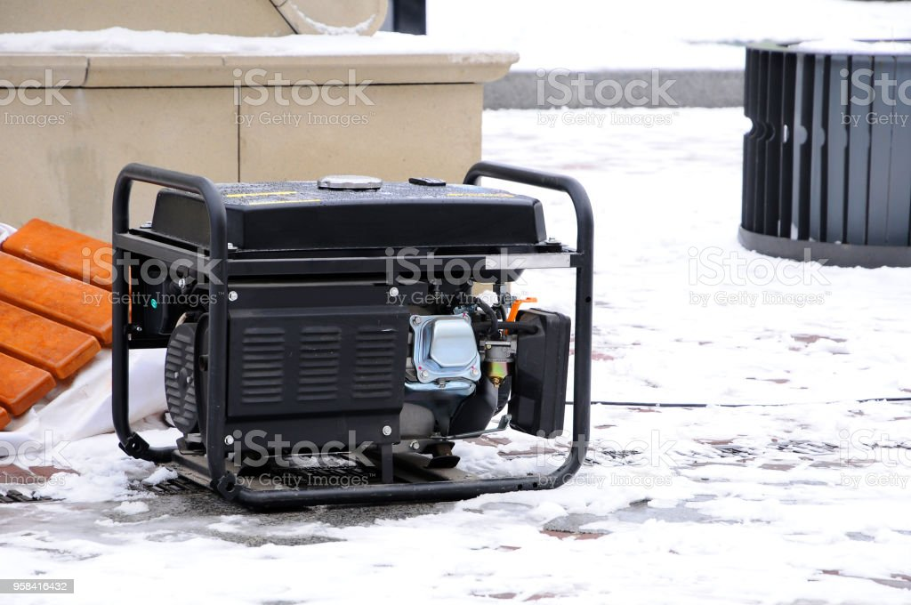 Portable electric generator running in the cold winter. stock photo