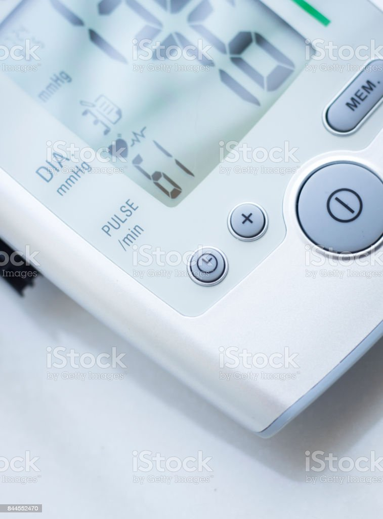Portable hand held domestic cardiac blood pressure and irregular heart beat pulse rate meter to show resting heart rate in monitored patient. stock photo