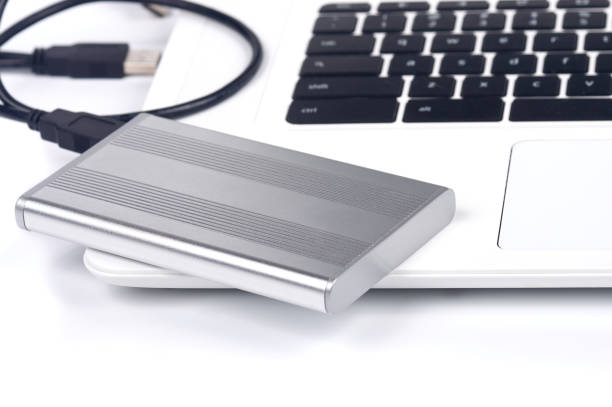 portable hard disk Metal case USB portable hard drive sitting on a white laptop external hard disk drive stock pictures, royalty-free photos & images