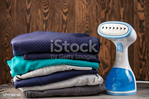 istock Portable home and travel garment steamer for clothes. Clothes pile. Housework 1214163133