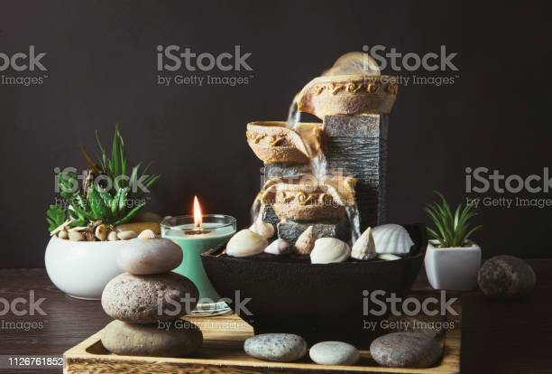 Photo of Portable indoor fountain for good Feng Shui in Your Home concept. Portable indoor small tabletop fountain. Spiritual mind and soul balance concept. Green plants in flower pot on background.