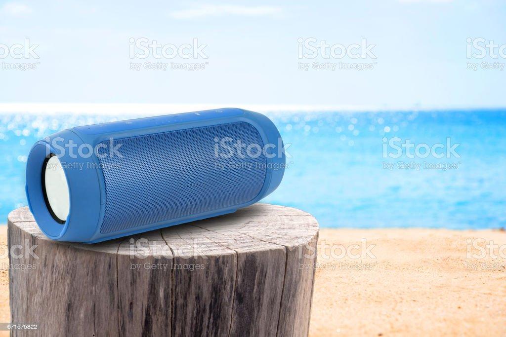 altavoz portátil en tocón mesa arenosa playa. - foto de stock