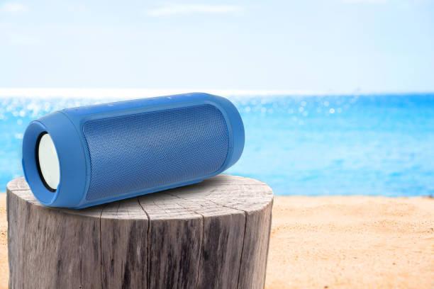 portable speaker on Stump table and sandy beach. stock photo