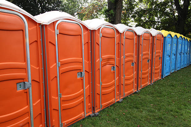 Portable toilets Colorful outdoor sanitation facilities set up in a park for the use of visitors to an outdoor festival. portable toilet stock pictures, royalty-free photos & images