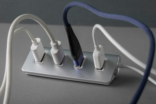 Portable USB hub for four connections with usb cables  on a white background. Bus povered. Closeup, selective focus