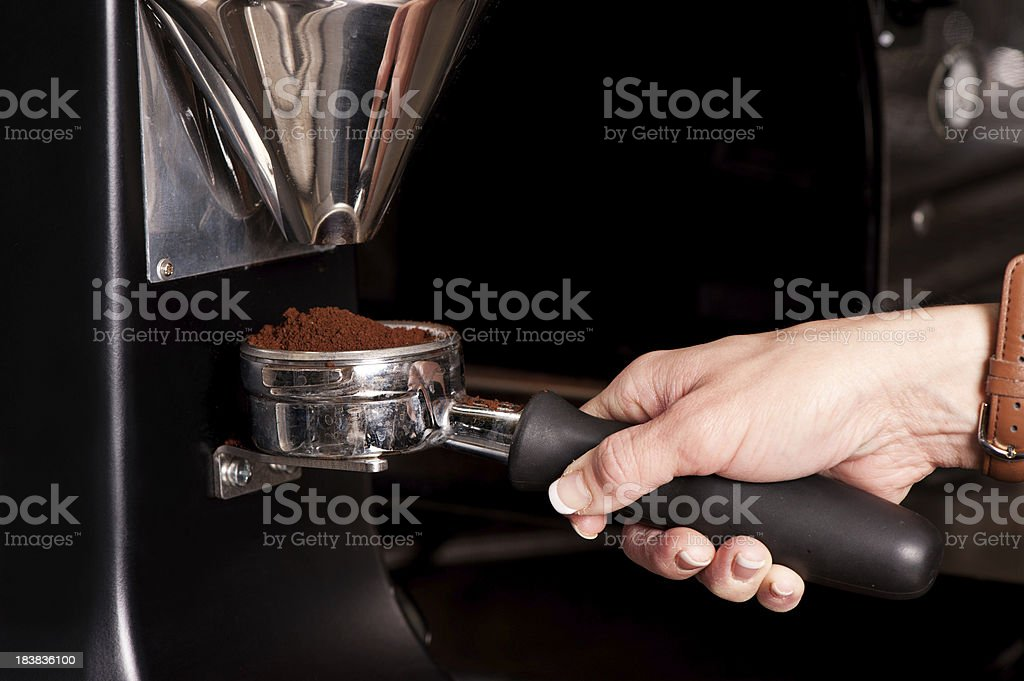 Portafilter catching coffee grounds from a grinder royalty-free stock photo