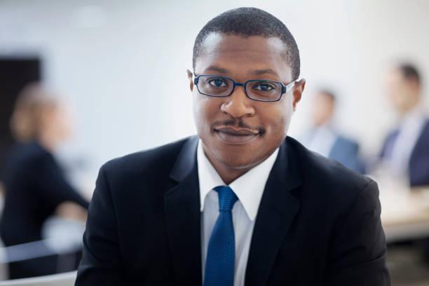 Porträt des Geschäftsmannes, der im Sitzungssaal sitzt – Foto