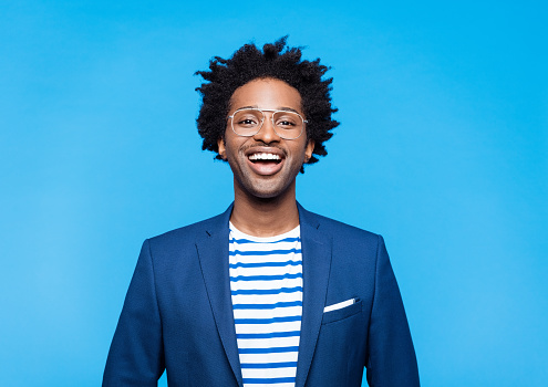 Happy afro american man wearing blue jacket, striped t-shirt and glasses smiling at camera. Studio shot on blue background. Portrait of designer.