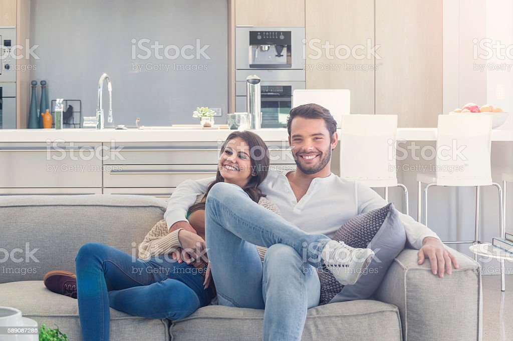 Portait of couple relaxing on the sofa. stock photo