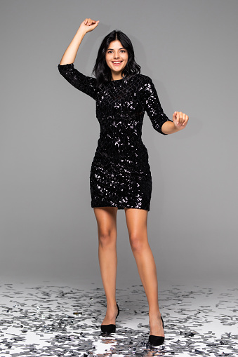 Portait of happy exited woman wearing evening black dress around confetti over isolated background with true happy emotions.