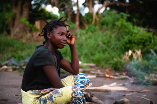 portait of young african woman sitting on the ground stock photo