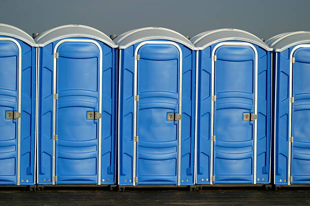 Portapotty Row of 5 portapotties at an outdoor event. portable toilet stock pictures, royalty-free photos & images