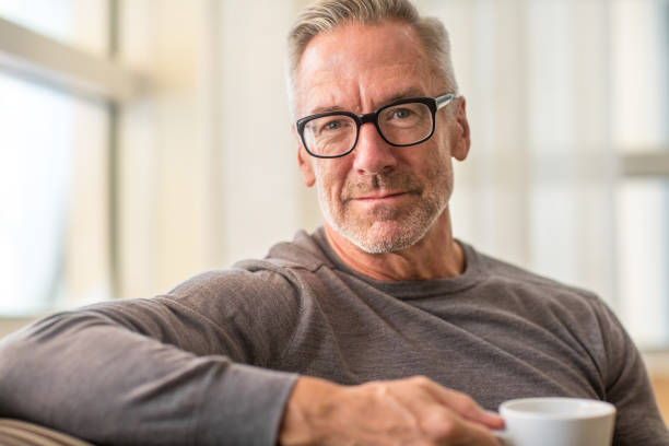 Portarit of a handsome older man drinking coffee stock photo