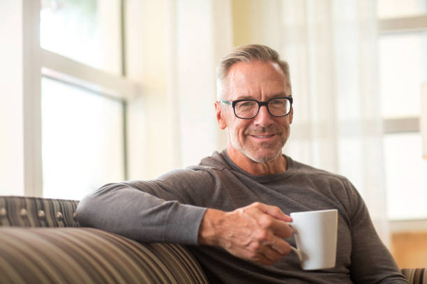 Portarit of a handsome older man sitting on a sofa stock photo