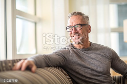 Portrait of a handsome older man looking out a window