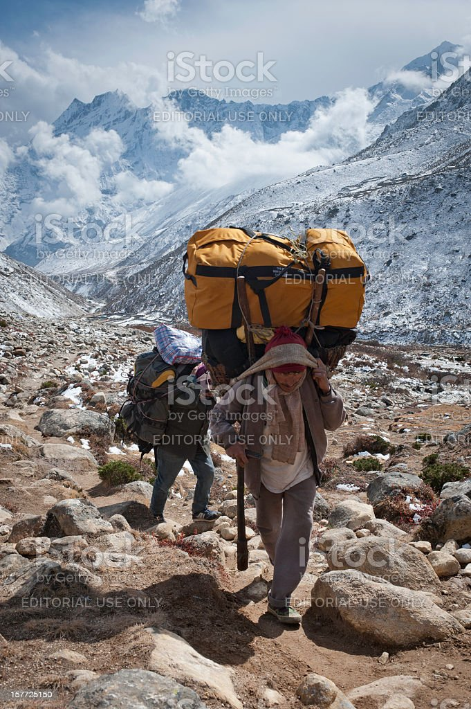 Porter carrying expedition bags mountain trail Himalayas Nepal stock photo