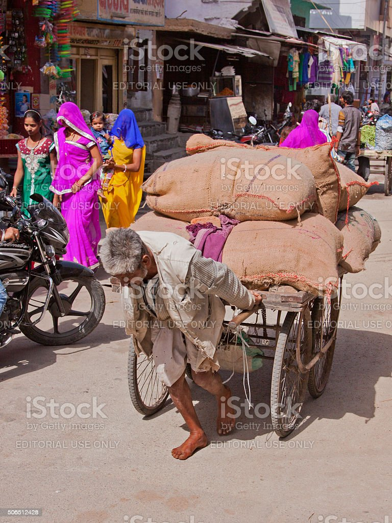 Porter moving a heavy load through a Rajasthani market place stock photo