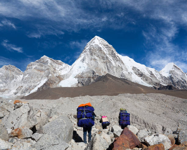 Porters carrying a heavy load to Everest Base camp stock photo