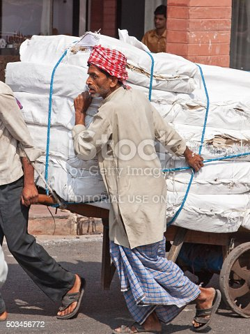 Delhi, India - March 22, 2014: Heavy load being moved by porters  through traffic in the heart of the old city. The use of porters to transport goods consignments in this way is common in Indian towns and cities