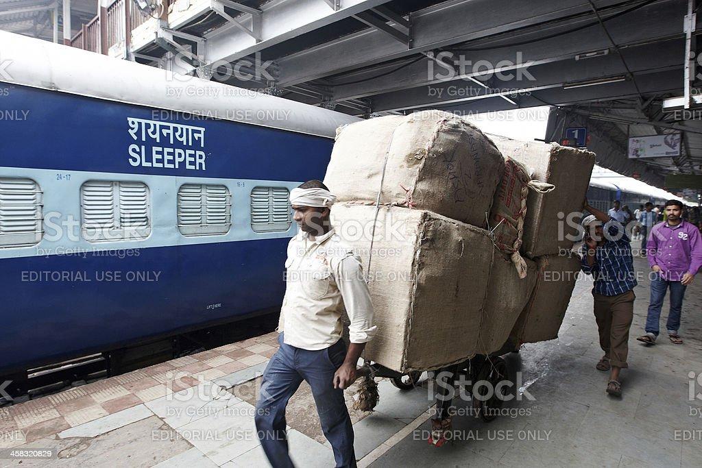 Porters pulling large handcart at Varanasi railway station royalty-free stock photo