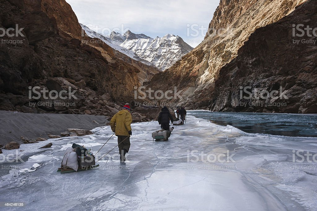 Porters walking on frozen Zanskar river, Ladakh, Northern India stock photo