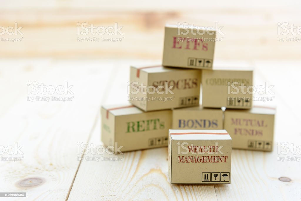 Portfolio and wealth management with risk diversification concept : Small paper cartons / boxes of financial instruments i.e ETFs, REITs, stocks, bonds, mutual funds and commodities, on a wood table. stock photo